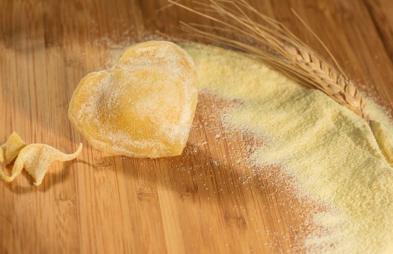 Des ravioli faits maison simples sous forme de coeur avec une oreille de blé et quelques unes de farine photo libre de droits