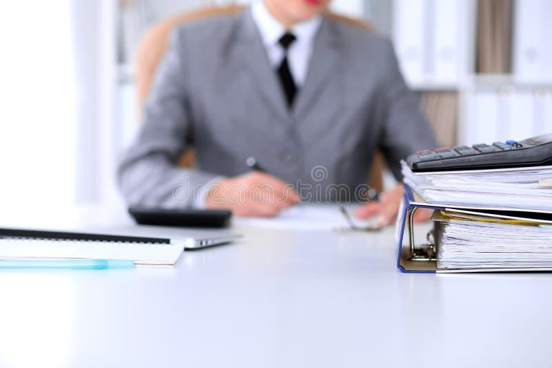 Des reliures avec des papiers attendent pour être traitées avec le dos de femme d'affaires dans la tache floue Budget de planific images stock