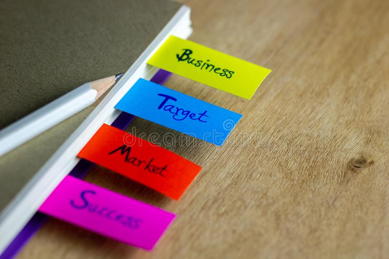 Des repères colorés sont écrits pour des affaires, cible, marché, succès, et ont un crayon blanc images libres de droits