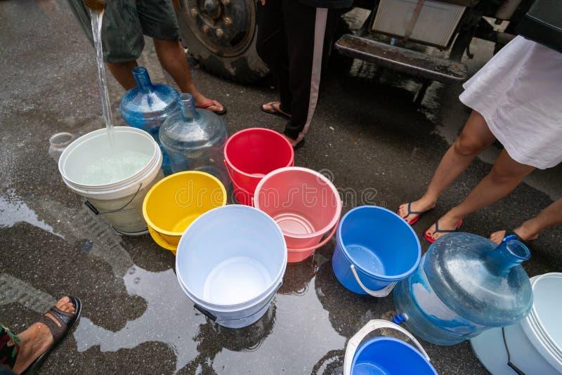 Des seaux d'eau vides attendent de l'eau douce du camion-citerne mobile d'urgence photographie stock libre de droits