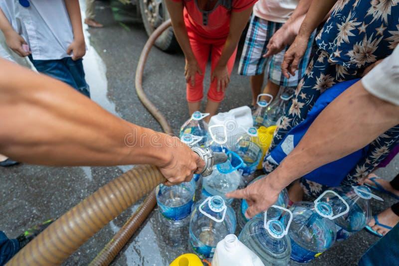Des seaux d'eau vides attendent de l'eau douce du camion-citerne mobile d'urgence photos libres de droits