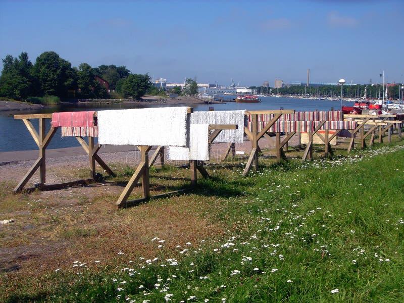 Des tapis et des nattes sont séchés sur le soleil sur le quai de la ville Helsinki photos libres de droits