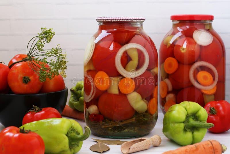 Des tomates marinées aux oignons, aux poivrons et aux carottes dans des boîtes sont situées sur un fond blanc images libres de droits
