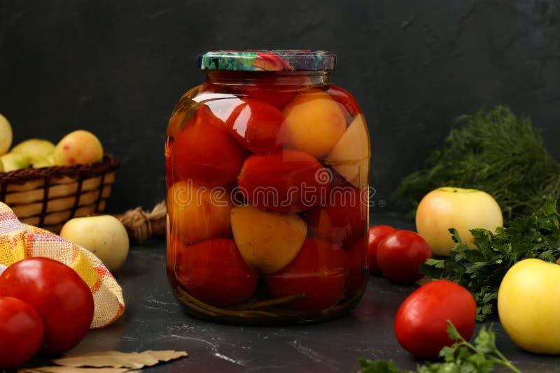 Des tomates marinées dans le pot sont situées sur un fond foncé image stock