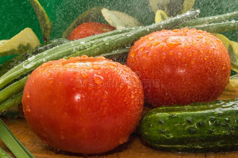 Des tomates rouges mûres, concombres verts, des plumes d'oignon vert sont couvertes de grandes gouttes de l'eau photographie stock