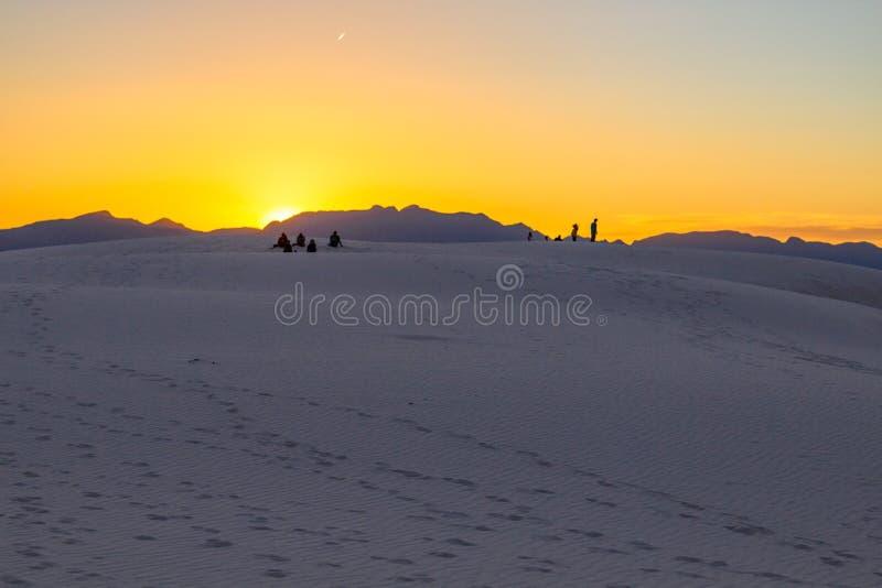 Des Touristes Se Tenant Sur Une Dune De Sable Regardant Un Coucher De Soleil Désert photographie stock libre de droits