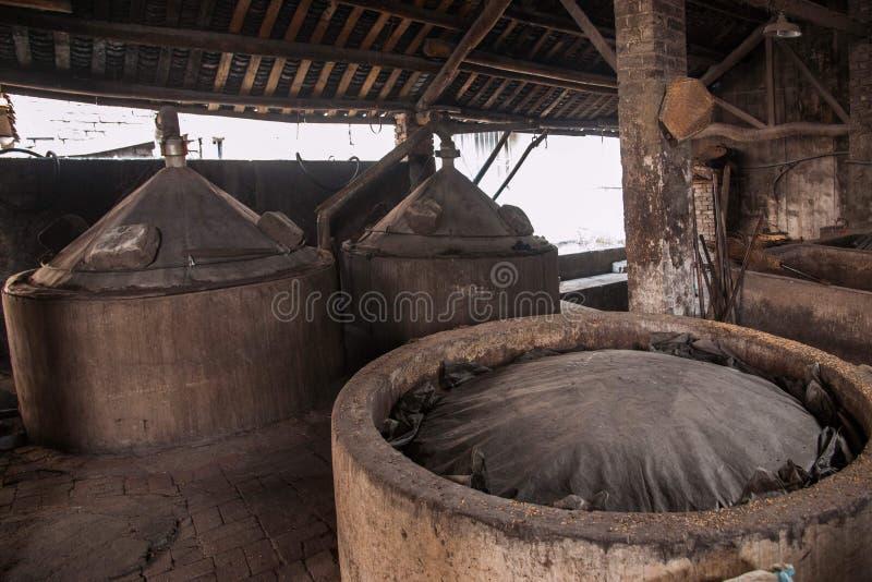 Des travailleurs de brasserie de ville de Leshan Qianwei Rochester sont placés dans l'étang de fermentation de lie de fermentatio photo libre de droits