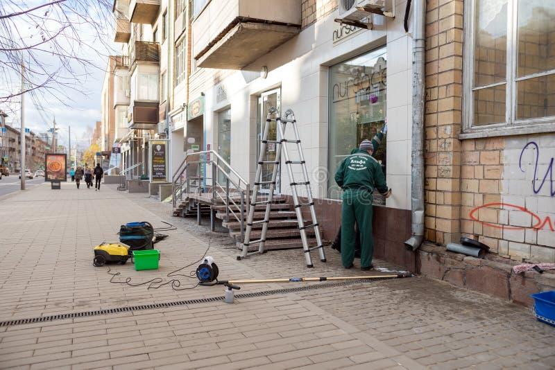 Des travailleurs de la société de nettoyage sont occupés les fenêtres de lavage et à nettoyer la façade après la réparation d'un  photos stock
