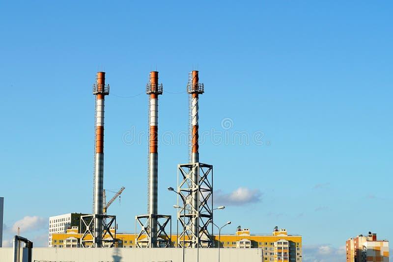 Des tuyaux contre un ciel bleu sont placés dans une rangée Tuyaux blancs et rouges du centre de chauffage, dans une ville sans fu image libre de droits