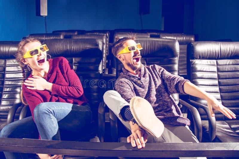 Des verres de type et de fille 3d sont très inquiétés tout en observant un film dans un cinéma photo stock