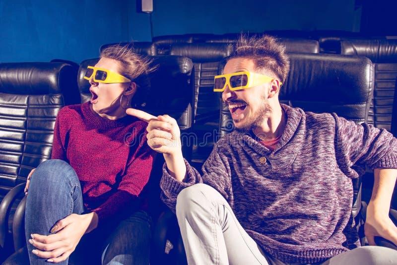 Des verres de type et de fille 3d sont très inquiétés tout en observant un film dans un cinéma images libres de droits