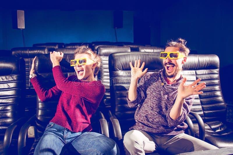 Des verres de type et de fille 3d sont très inquiétés tout en observant un film dans un cinéma image libre de droits