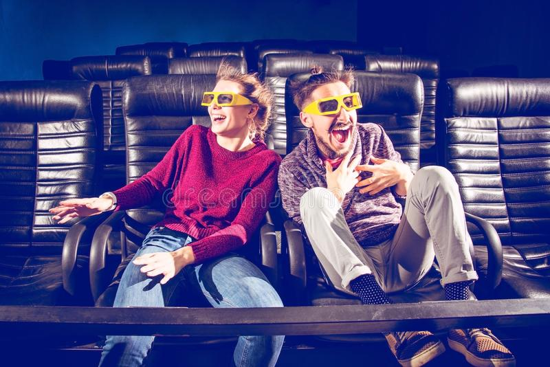 Des verres de type et de fille 3d sont très inquiétés tout en observant un film dans un cinéma images stock