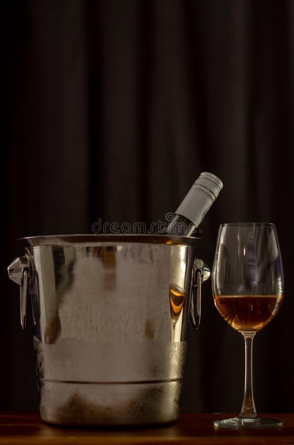 Des verres de vin de Rose sur la table en bois avec une bouteille dans un seau plus froid de vin images libres de droits