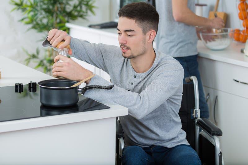 Desabilitou o homem novo na cadeira de rodas que cozinha na cozinha fotos de stock