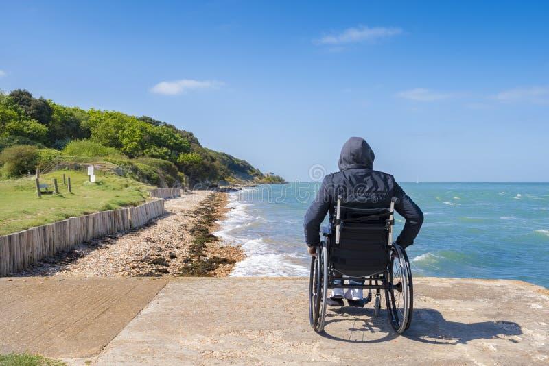 Desabilitou o homem novo que senta-se em uma cadeira de rodas e em olhares no mar foto de stock royalty free