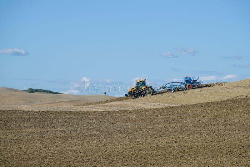 Desafiador seguido MT765D del tractor con el taladro de semilla neumático Lemken Solitair 9 en el campo en un Septem soleado fotografía de archivo libre de regalías