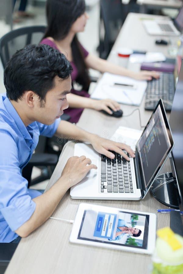 Desarrollador de software asiático que usa el ordenador portátil fotos de archivo libres de regalías