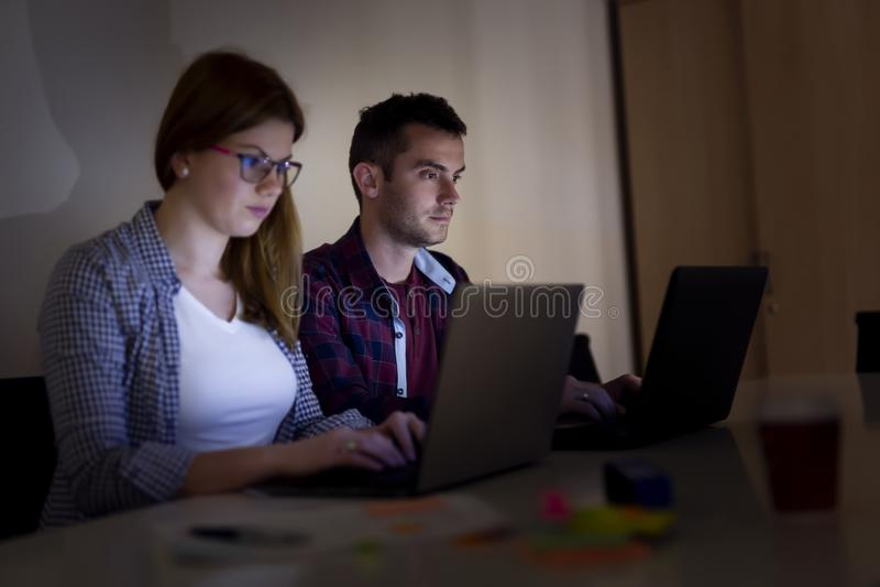 Desarrolladores de software que trabajan en horas extras imagen de archivo