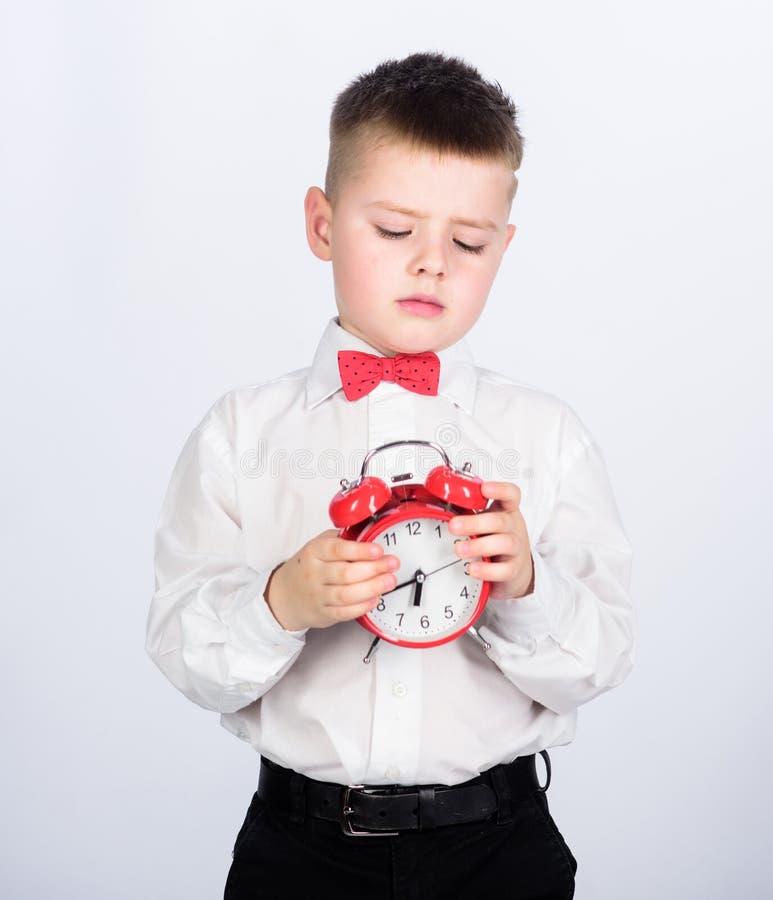 Desarrolle la autodisciplina Ponga el despertador Reloj rojo del control del ni?o peque?o del ni?o Es tiempo Horario y sincroniza fotografía de archivo