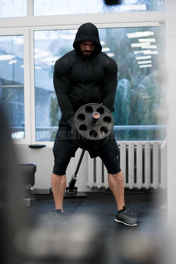Desarrollo físico de un joven fuerte que empuja pesados bárbaros en el gimnasio deportivo imagenes de archivo