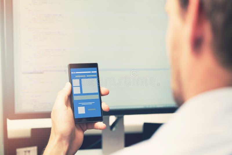 Desarrollo móvil del app - teléfono elegante con el wireframe del uso foto de archivo