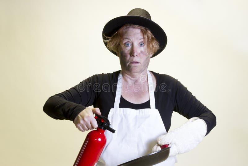 Desastre de la cocina, sombrero del peregrino y extintor imágenes de archivo libres de regalías