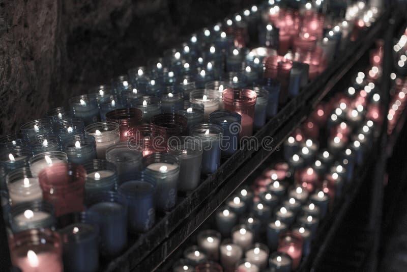 Desaturated крупный план красочных свечей горя в тоннеле Covadonga, Cangas de Onis, Астурии, Испании Духовность стоковые фото