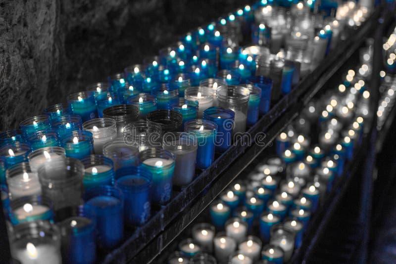 Desaturated blaues Bild einer Nahaufnahme der bunten Kerzen, die im Tunnel von Covadonga, Cangas de Onis, Asturien, Spanien brenn stockfoto