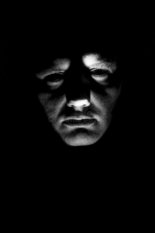 Desaturated mensen` s gezicht van onderaan met flitslicht wordt verlicht dat stock afbeeldingen