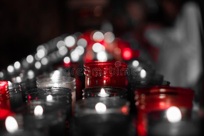 Desaturated rotes Bild einer Nahaufnahme der bunten Kerzen, die im Tunnel von Covadonga, Cangas de Onis, Asturien, Spanien brenne lizenzfreie stockbilder