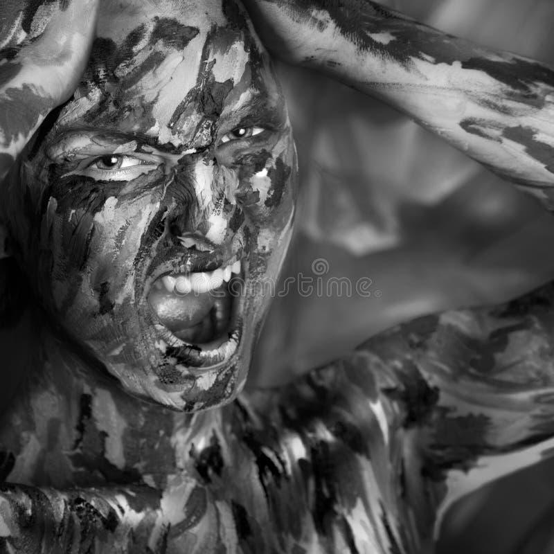 Desaturated stående av den emotionella kvinnan i målarfärger arkivbild