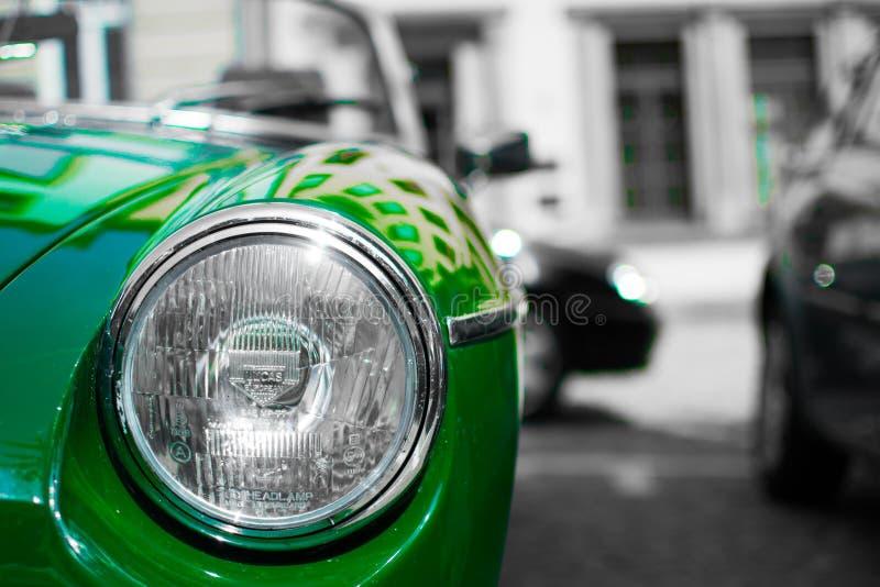 Desatured-Foto eines Abschlusses oben des Scheinwerfers eines grünen klassischen Sportwagens, mit unscharfem Schwarzweiss-Hinterg stockfotos