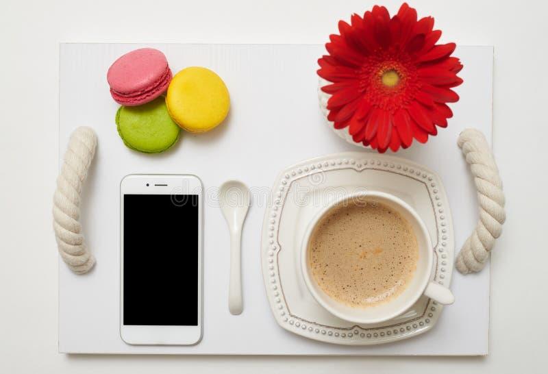 Desayune con café, los macarrones y el teléfono móvil en la bandeja fotografía de archivo