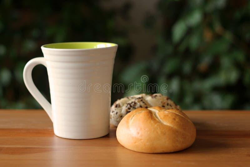 Desayune con café y el bollo recientemente cocido del kaiser de la semilla de amapola en la tabla de madera Fondo enmascarado Con imagen de archivo libre de regalías