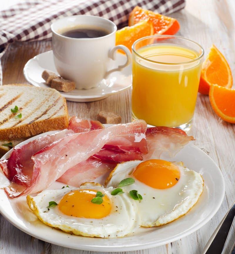 Desayune con dos huevos fritos, tocinos, tostadas, jugos y cafés foto de archivo libre de regalías