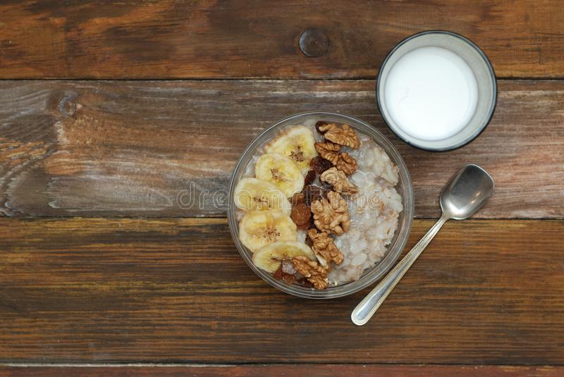 Desayune con el cuenco del Granola, Muesli con la avena, las nueces y los frutos secos, leche, en la tabla de madera Bannana, nue imagen de archivo