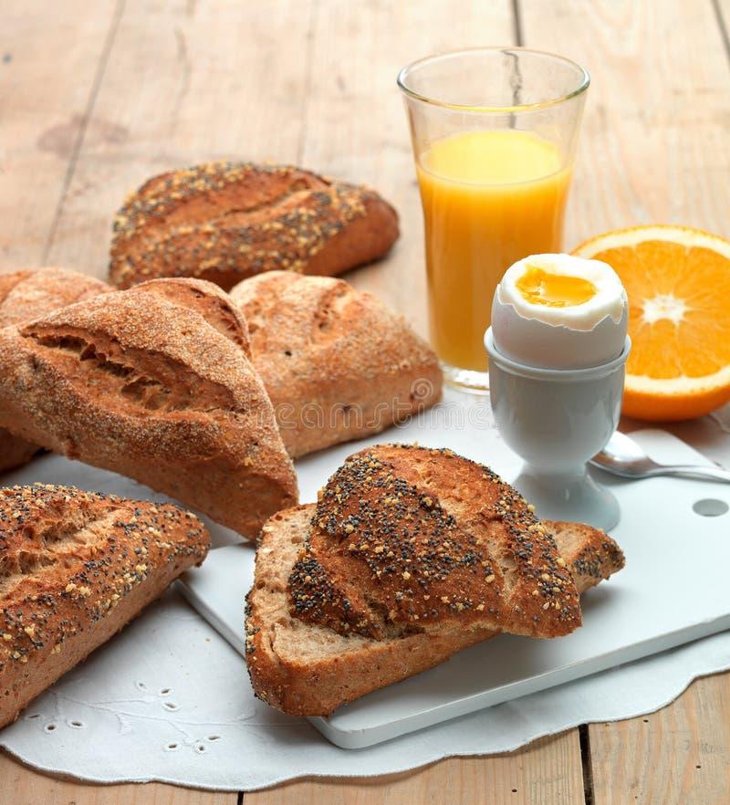 Desayune con el huevo, el zumo de naranja y los rollos fotos de archivo libres de regalías