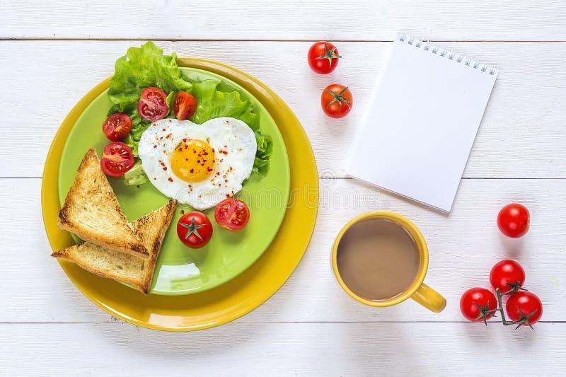 Desayune con el huevo frito en forma de corazón, tostada, tomate de cereza, deje imagenes de archivo