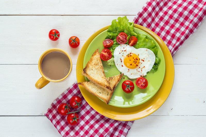 Desayune con el huevo frito en forma de corazón, tostada, tomate de cereza, deje imagen de archivo libre de regalías