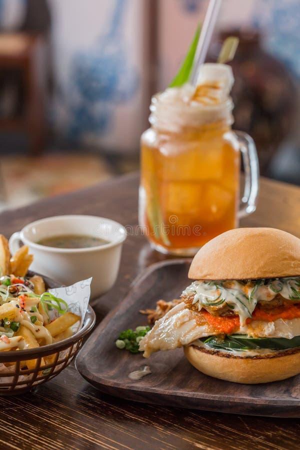 Desayune con la hamburguesa, la cesta de ensalada y el té de la fruta imagen de archivo