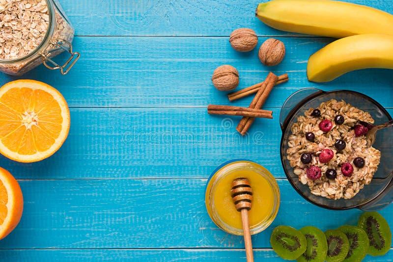 Desayune con la harina de avena, las bayas, la miel, las frutas y las nueces Espacio para el texto foto de archivo libre de regalías