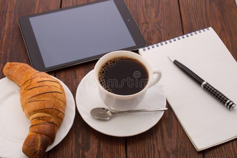 Desayune con la taza de café sólo, de cruasanes y de cuaderno imagen de archivo