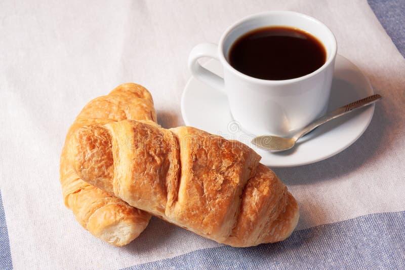 Desayune con la taza de café sólo y de cruasanes foto de archivo