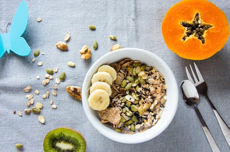 Desayune con las nueces, la papaya y el kiwi con una mariposa plástica imagenes de archivo
