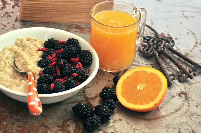 Desayune con las zarzamoras, las semillas del goji y el zumo de naranja imágenes de archivo libres de regalías