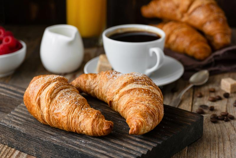 Desayune con los cruasanes, el café, el zumo de naranja y las bayas imagen de archivo