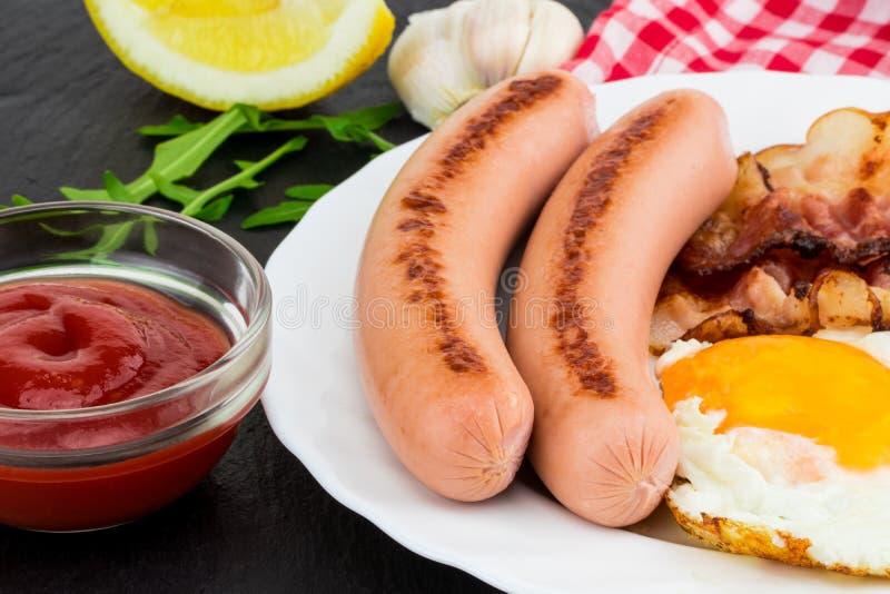 Desayune con los huevos fritos, el tocino, las salchichas y la ensalada vegetal o fotos de archivo libres de regalías