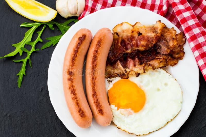 Desayune con los huevos fritos, el tocino, las salchichas y la ensalada vegetal o fotografía de archivo libre de regalías
