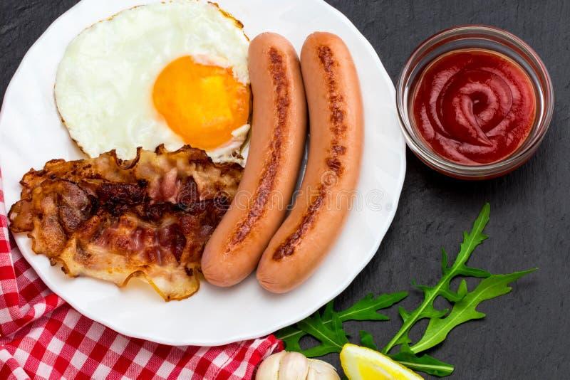 Desayune con los huevos fritos, el tocino, las salchichas y la ensalada vegetal o foto de archivo